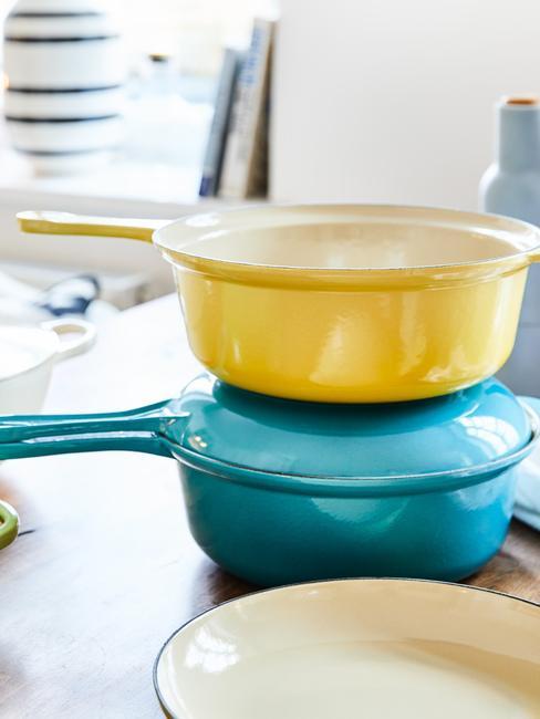 Dwa, kolorowe garnki żeliwne sotjące jeden na drugim w kuchni