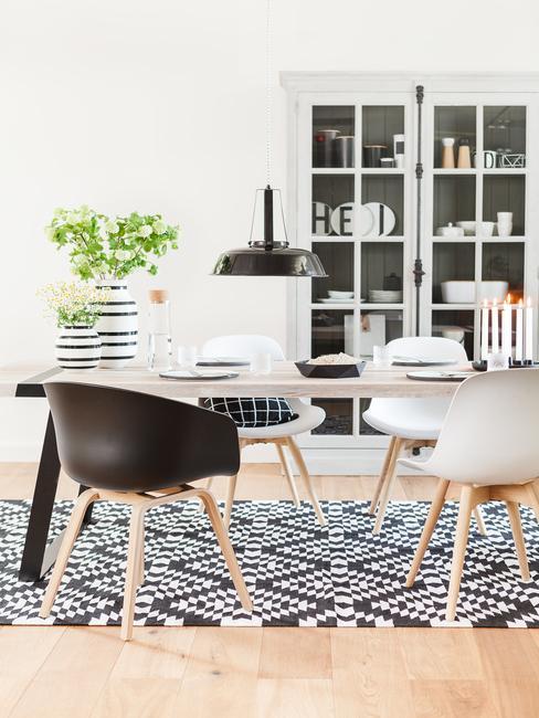 Jadalnia z prostokątnym, drewnianym stołem, czterema krzesłami oraz czarnym dywanem w romby