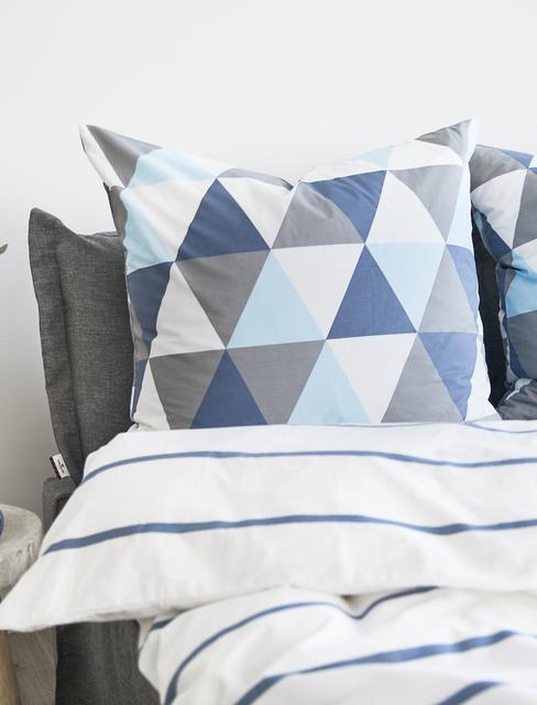 Zbliżenie na łóżko z pościela we wzory geometryczne