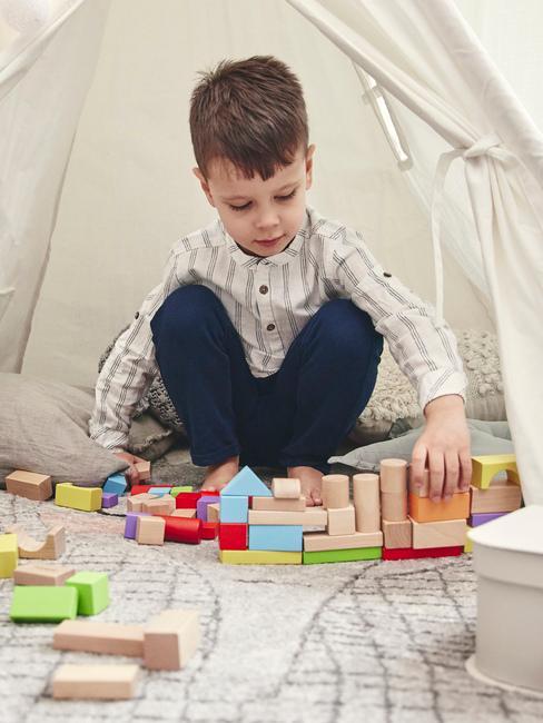 Chłopczyk siedzący pod namiotem i bawiący się zabawkami