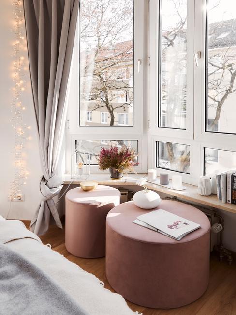Fragment sypialni z dwoma różowymi pufami jako stolikami oraz dekoracje ustawione na parapecie