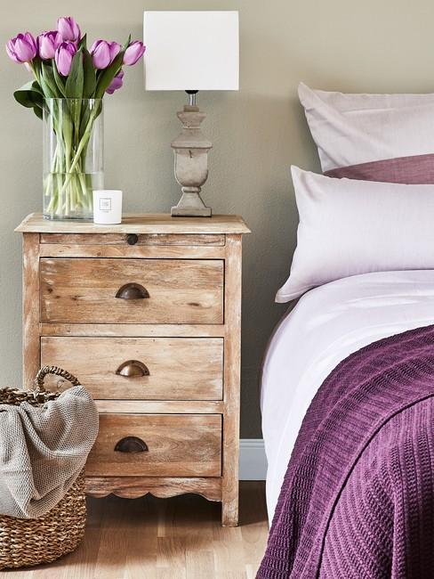 Fregment sypialnia z drewnianym stolikiem nocnym z lampą oraz wazonem kwiatów oraz łożkiem z fioletową narzutą