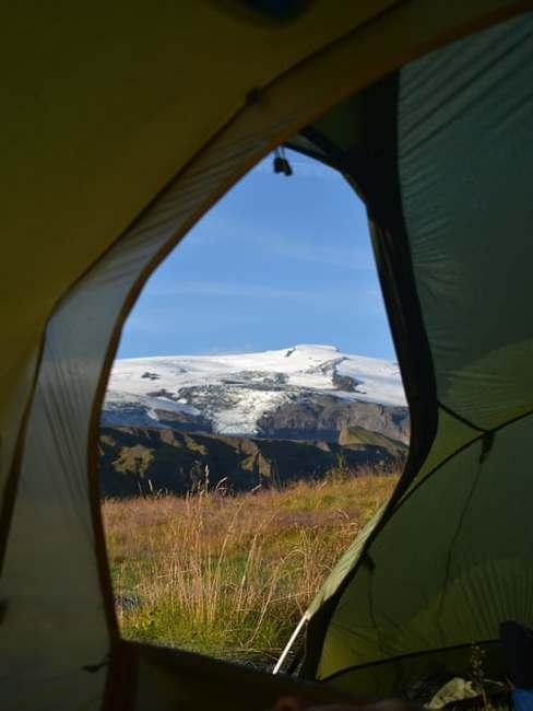 Namiot rozłożony na polanie z otwarym wejściem z widokiem na górę