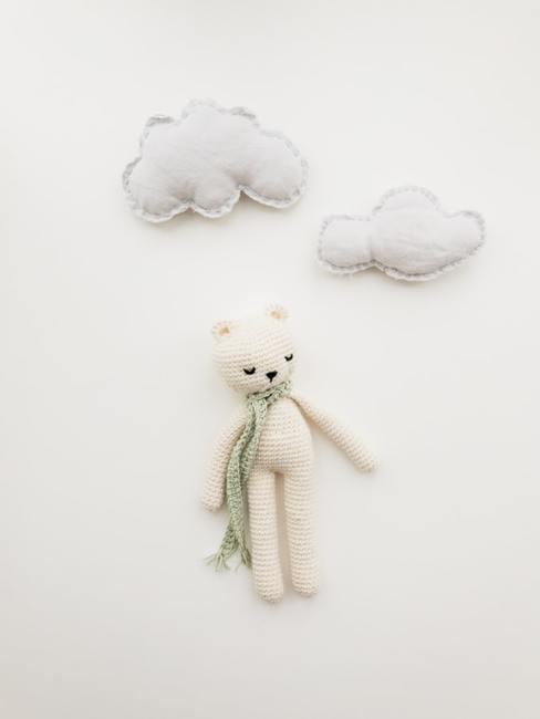 Dziergany, biały miś powieszony na białejj ścianie w kąciku dla niemowlaka