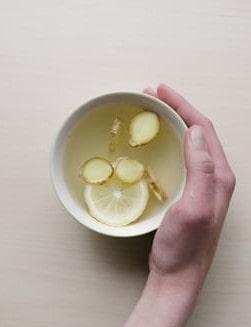 Biały kubek z naparem z cytryny i imbiru