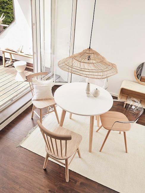 Jasna jadalnia z okrągłym stołem i czterema, drewnianymi krzesłami połączona z tarasem