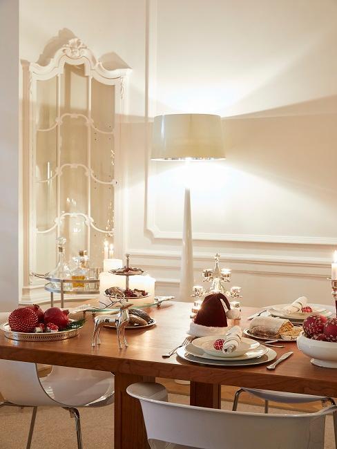 Oświetlona, biała jadalnia z prostokątnym, drewnianym stołem oraz zastawą