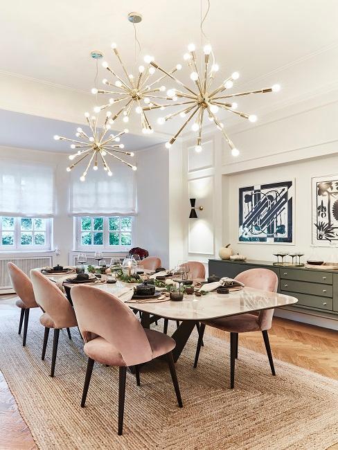 Jadalnia z beżowymi ścianami, ciemną komodą, dużym , marmurowym stołem oraz krzesłami z różowymi obiciami