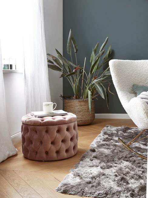 Salon z białą oraz zieloną ścianą, z rośliną, pufem w kolorze brudnego różu oraz białym fotelem