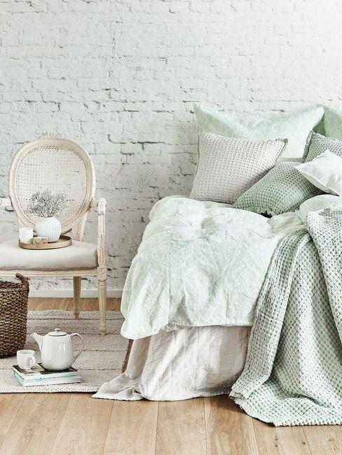 Sypialnia z miętowymi detalami i ścianą z tapetą imitującą białą cegłę