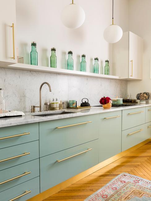 Fragment salonu z aneksem kuchennym z meblami o lekko turkusowym kolorze