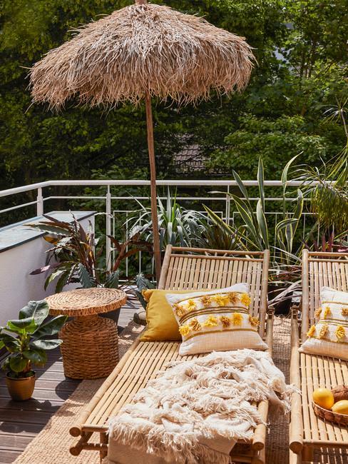 Taras ogrodowy z leżakami z bambusa, parasolem i rattanowym stoliczkiem