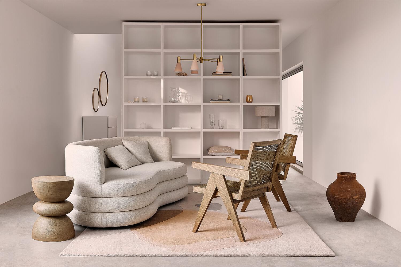 Jasny salon z biała sofą, drewnianymi krzesłąmi oraz białym regałem