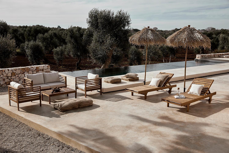 Taras z dwoma leżakami oraz drewnianym kompletem mebli ogrodowych w stylu śródziemnomorskim