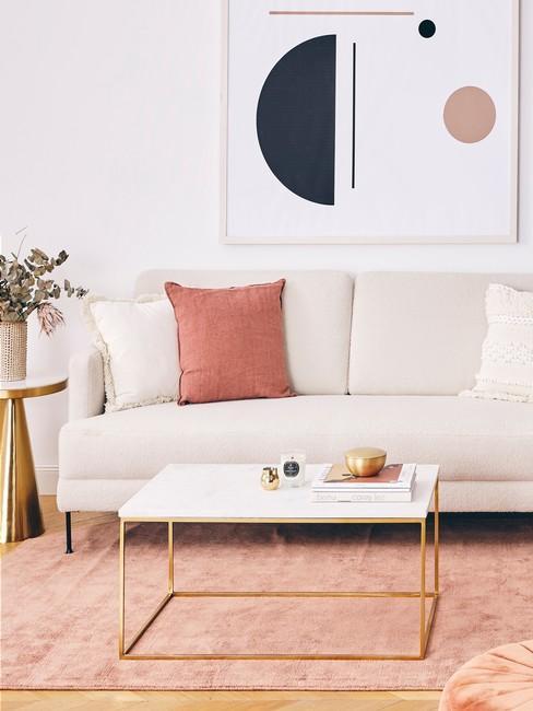 Salon z biała sofą, stolikiem, obrazem oraz tekstyliami