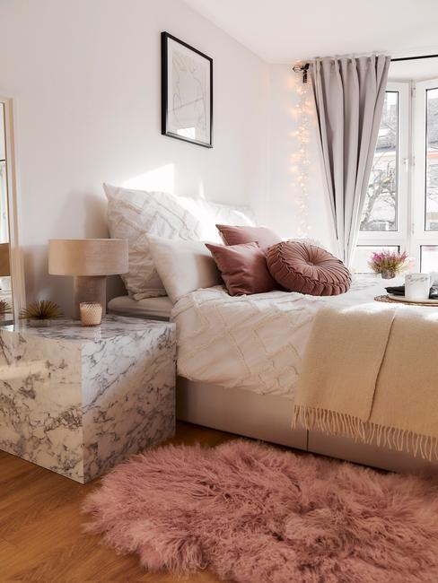 Salon z białą ścianą, łożkiem, marmurowym stoliczkiem oraz różowymi dekoracjami