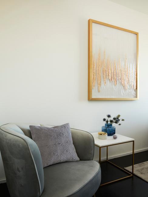 Beżowy salon z szarym krzesłem, bialtym stolikiem oraz wazonem z kwiatami