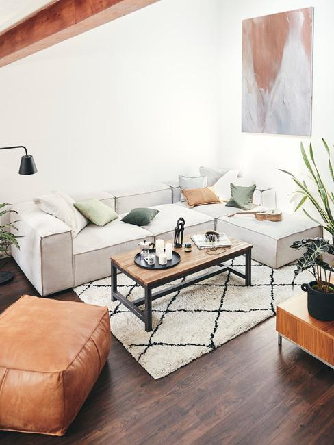Jasny salon z biłą ścianą, sofą oraz drewnianymi stolikami