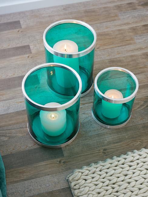 Trzy niebieskie lampiony ze świacami na podłodze
