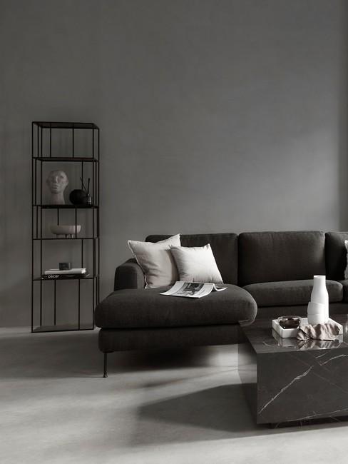 Salon z szarą ściną, czarną sofą oraz metalową, wąską szafą
