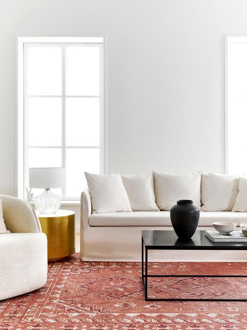 Biały salon z czerwonym dywanem, czarnym stolikiem oraz złotymi dekoracjami