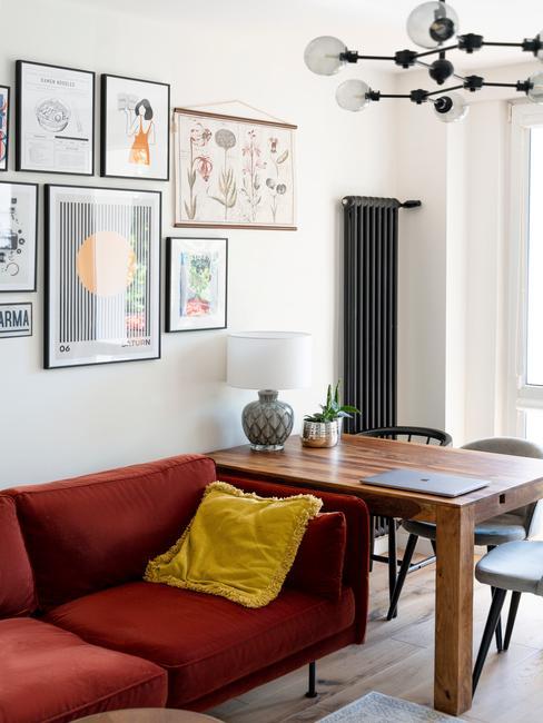 Biały salon z galerią zdjęć, czerwoną kanpą oraz drewnianym stołem