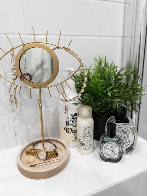 Lustarko w kształce oka oraz akcesoria kosmetyczne w łazience