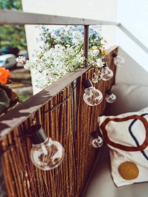 Fragment balkonu z grilandą świetlną, poduszką oraz rośliną