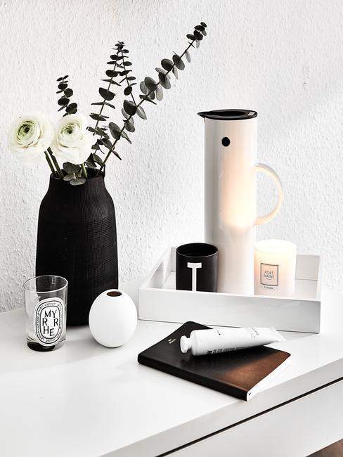 Biały termos ustawiony na tacy obok świeczek i czarnego wazonu