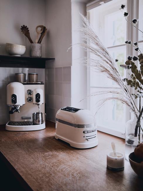 Beżowy toster kitchenaid na drewnianym blacie w rustykalnej kuchni