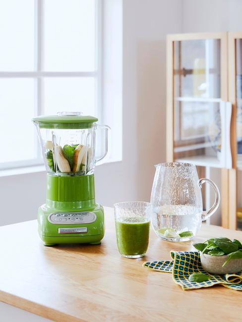Zielony blender KitchenAid obok transparentnej szklanki oraz karafki na wodę