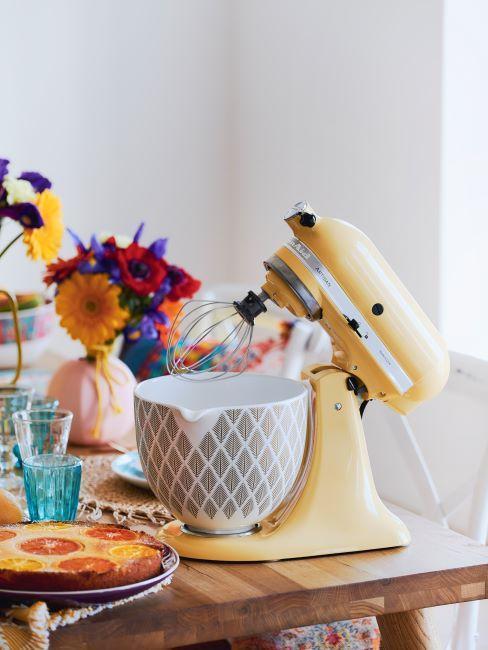Żółty robot planetarny kitchenaid z wzorzysta misą na blacie w kuchni