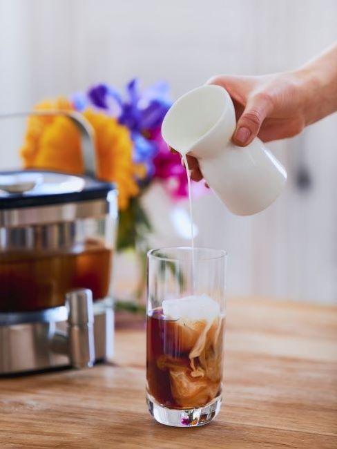 Szklanka z kawą obok ekspresu do kawy