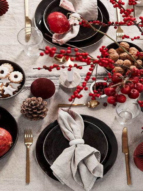 Stół udekorowany białym obrusem, czarną zastawą, syszkami oraz ciastkami