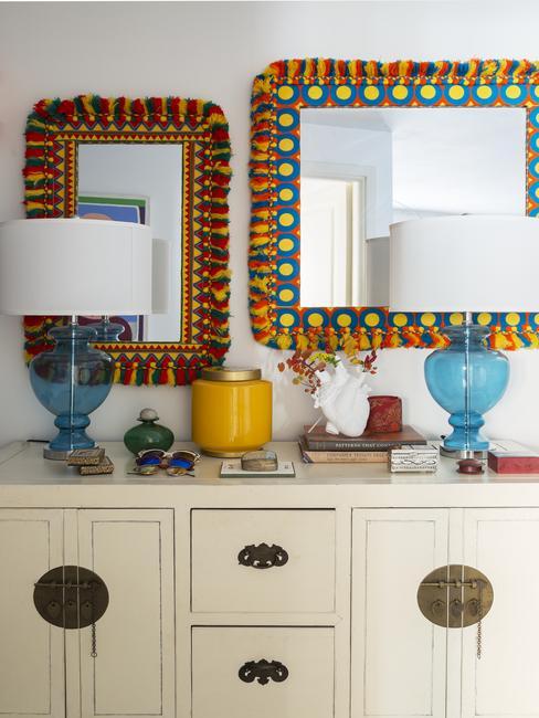 Biała komoda z niebieskimi lampkami, nad którą wisi lustro z kolorową ramą