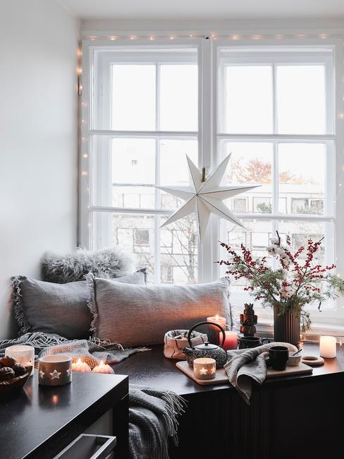 Czarny wykusz w mieszkaniu z trzema poduszkami, wazonem oraz filiżankami