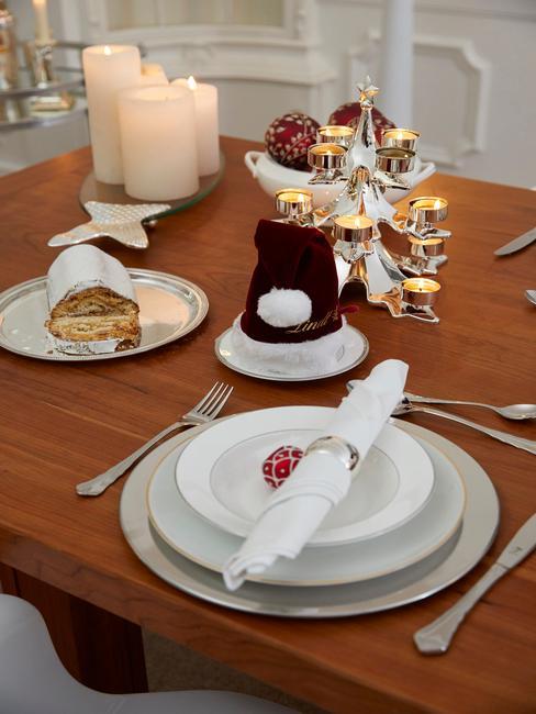 Klasyczna dekoracja stołu z białą zastawą, ciastem oraz stroikiem świątecznym