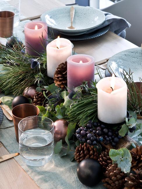 Wieniec adwentowy na stole wigilijnych z zielonych galązek i czterech świeczek