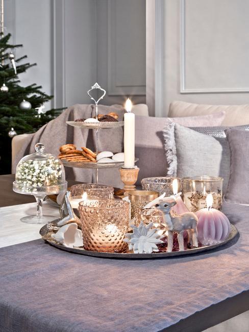 Taca dekoracyjna z ozdobami świątecznymi w postaci świeczek, małych dekoracji na różowym pufie w salonie