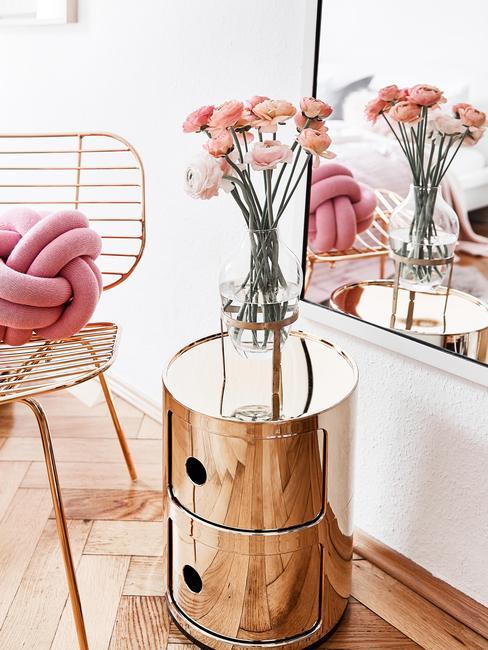 Zbliżenie na metalowy stolik nocny w złotym odcieniu z wazonem świeżych kwiatów