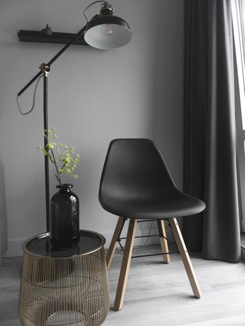Krzesło projektu Eames w czarnym kolorze na tle szarej ściany