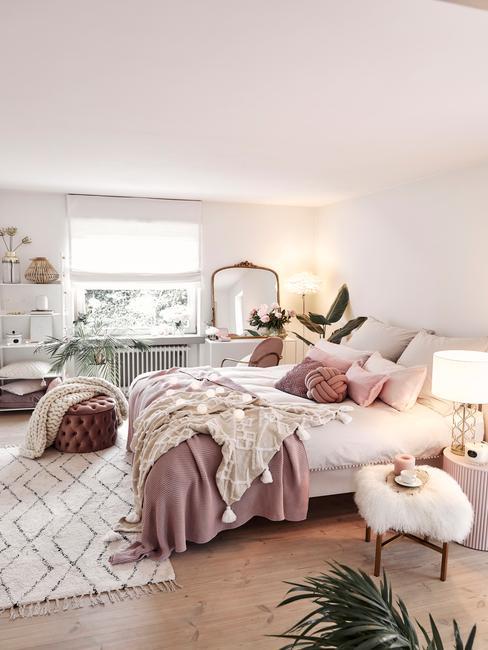 Biała sypialnia w stylu glam z łożkiem, kocami, pufem i rośliną