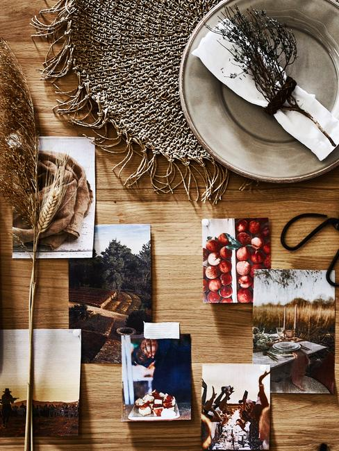 Stół na któym znajdują się zdjęcia, suszone kwiaty oraz talerz