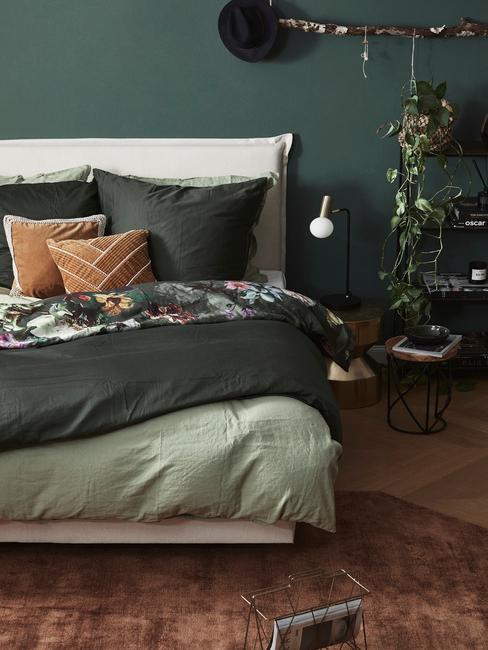Zielona sypialnia w stylu boho z łożkiem o białym zagłówku, zielonej pościeli oraz roślinie