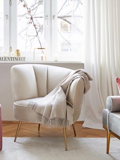 Beżowy fotel z kocem z wełny alpaki  jasnym pokoju