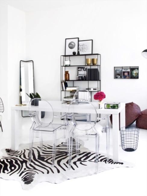 Stół i krzesła z plexi w jadalni. Całość utrzymana w czarno-białych kolorach.