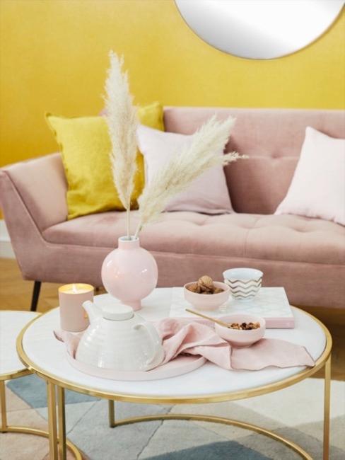 Różowa aksamitna sofa ozdobiona żółtymi poduszkami z jedwabiu na tle żółtej ściany