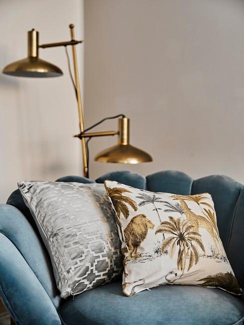Turkusowy fotel-muszla w salonie z dekoracyjnymi poduszkami i złotą lampą podłogową