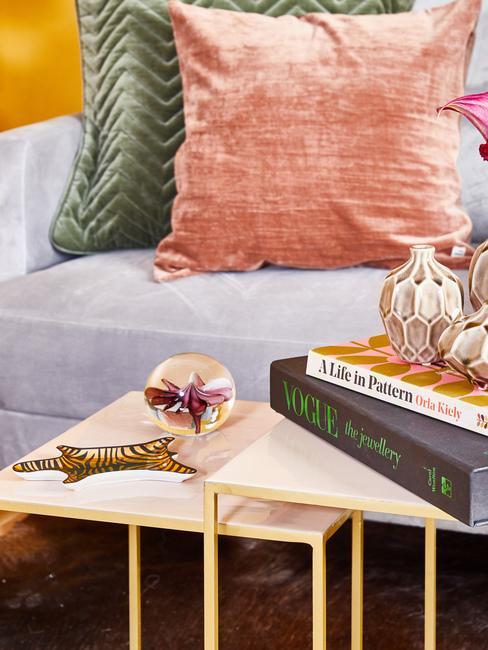 Zbliżenie na szarą sofę z szmaragdowozieloną i łososiową poduszka