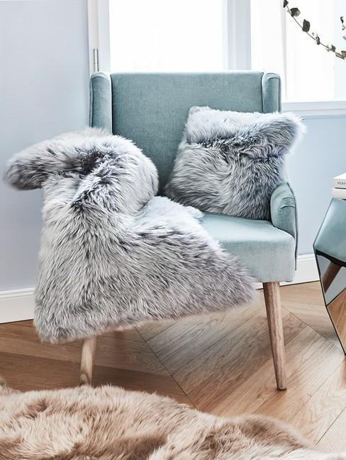 Zbliżenie na turkosowy, aksamitny fotel z szarym futrem